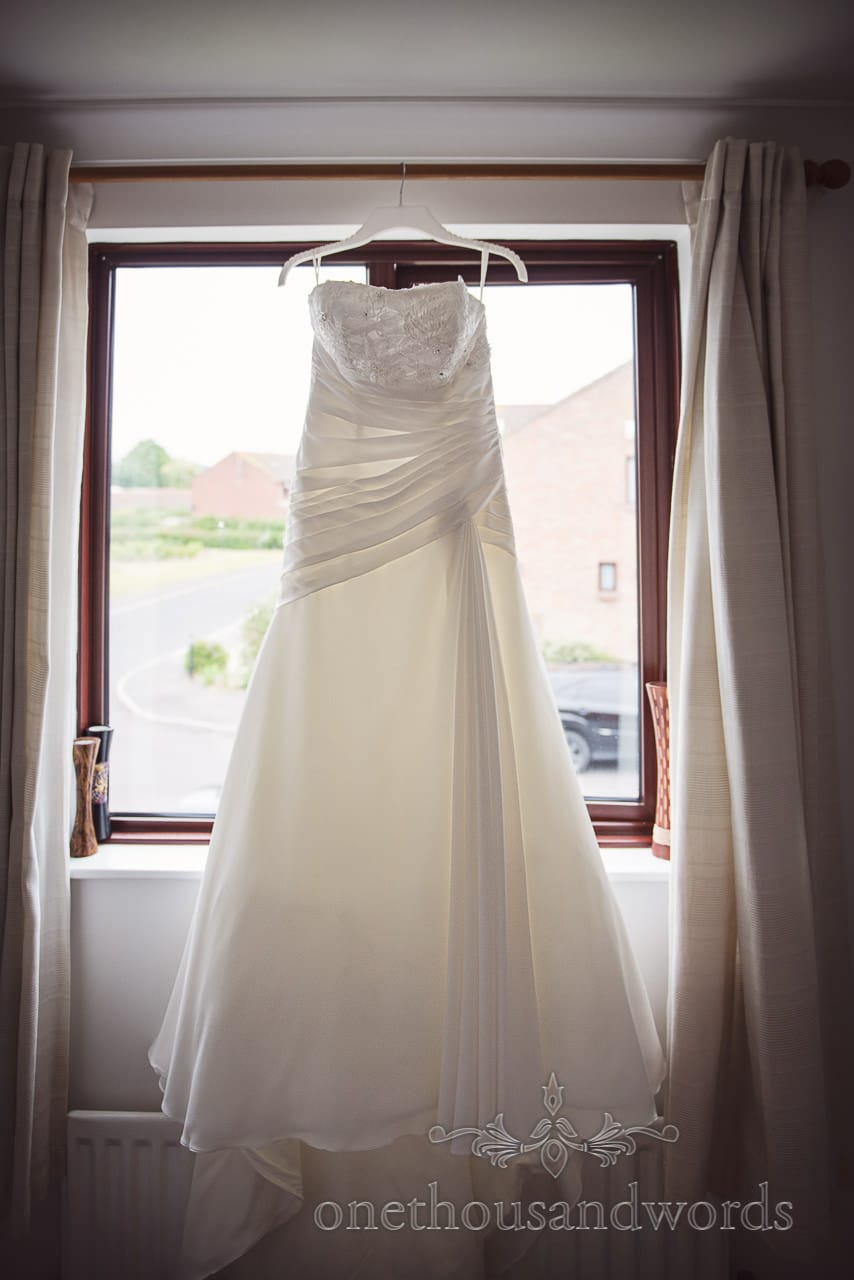White A-line strapless wedding dress with chest detailing hangs in window on wedding morning