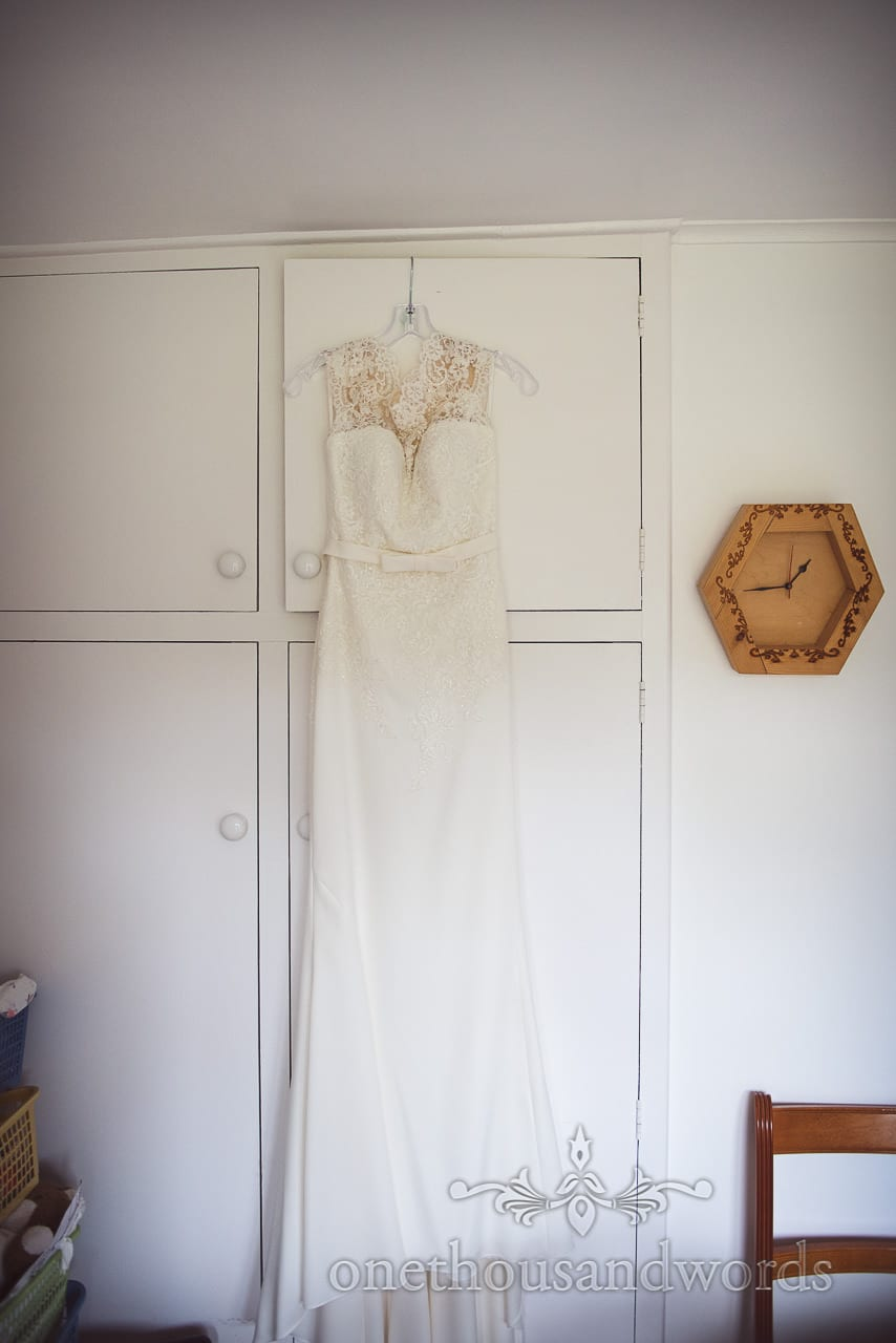 White lace detail dropped waist wedding dress hangs on wedding morning next to clock