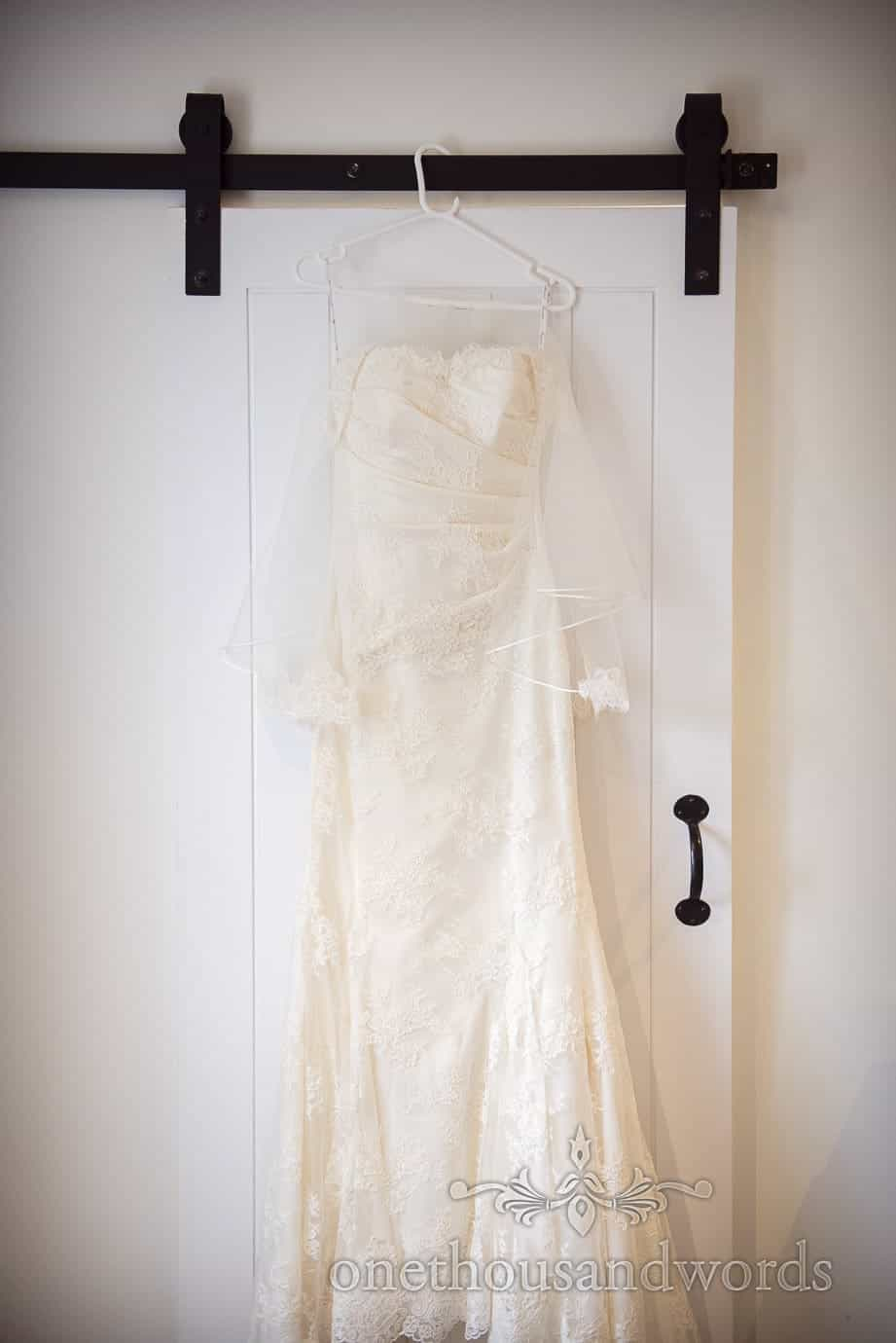 White trumpet wedding dress with lace detailing hangs on white door on wedding morning