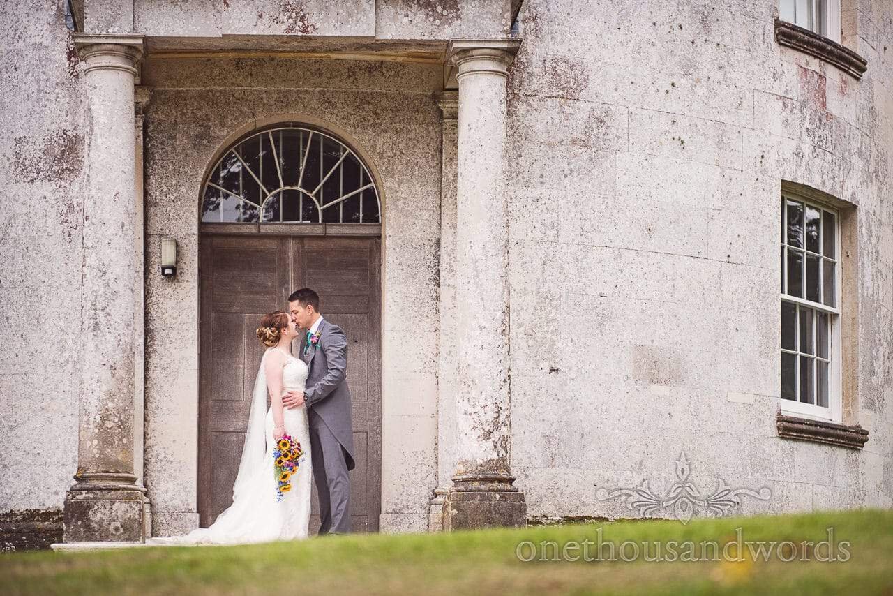 A kiss outside Catholic chapel at Lulworth Castle Wedding Photographs