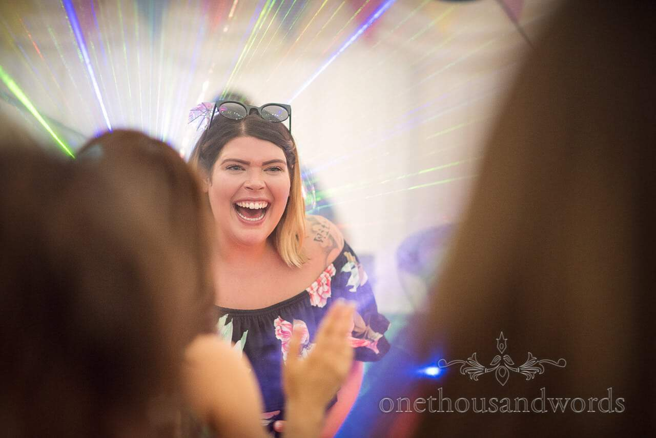 A smiling wedding guest among the lasers on dance floor