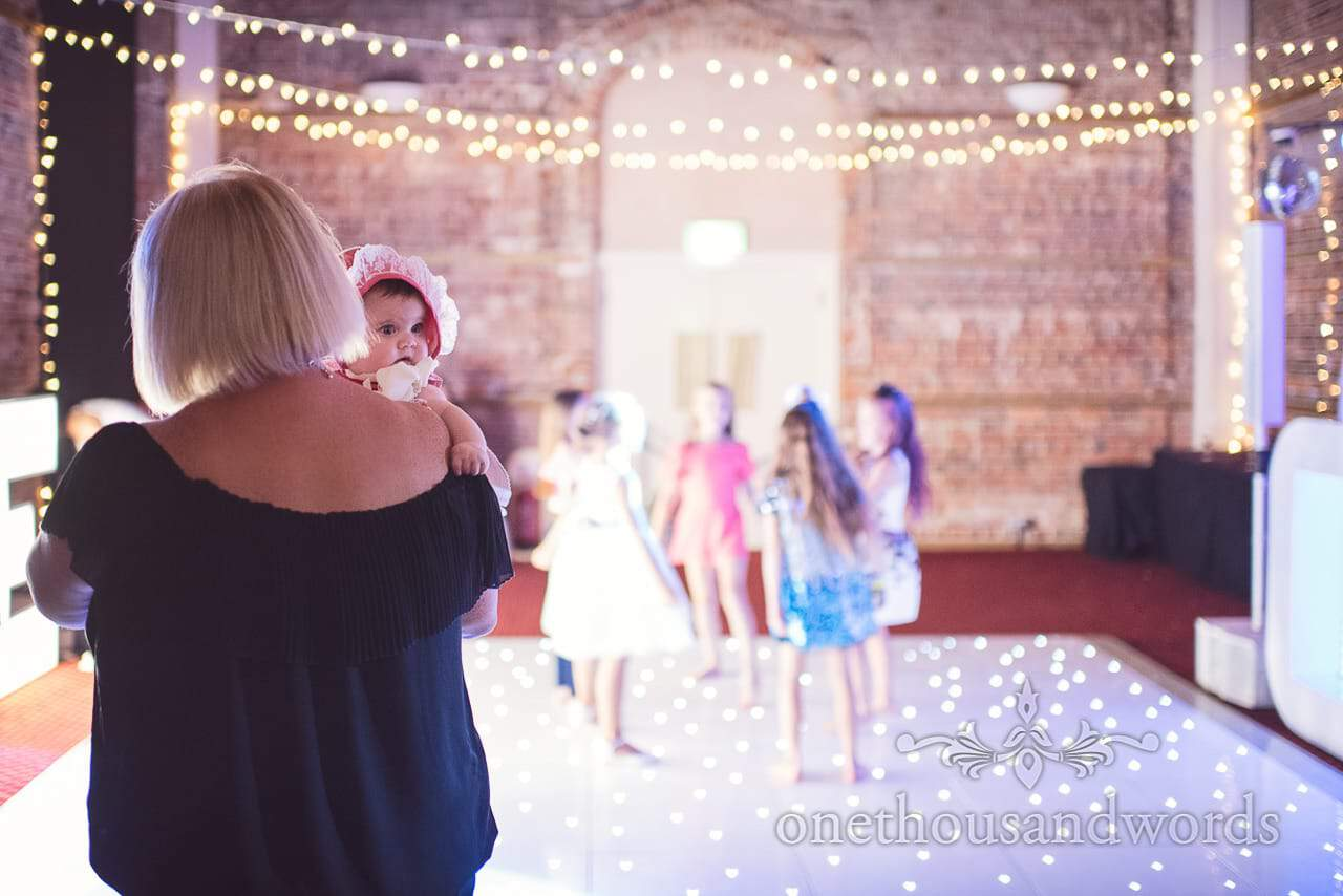 Baby in bonnet at Highcliffe Castle Wedding evening dance floor with fairy lights