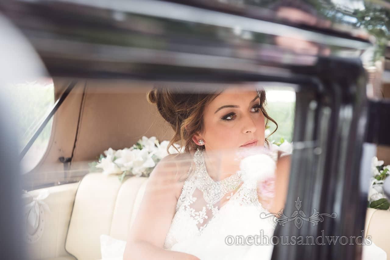 Beautiful bride looks through wedding car window at Highcliffe Castle Wedding