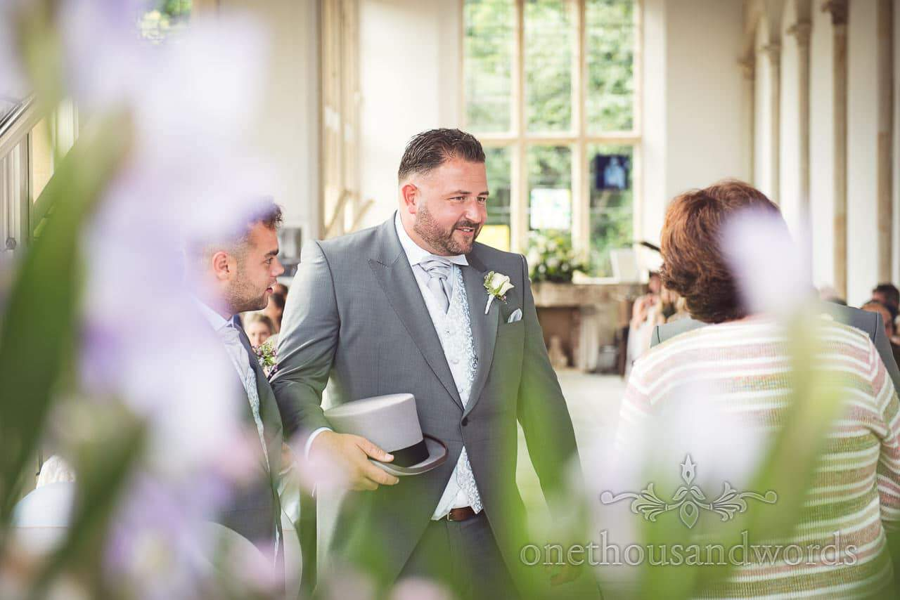 Best man in grey tail suit and top hat waits at Highcliffe Castle wedding ceremony