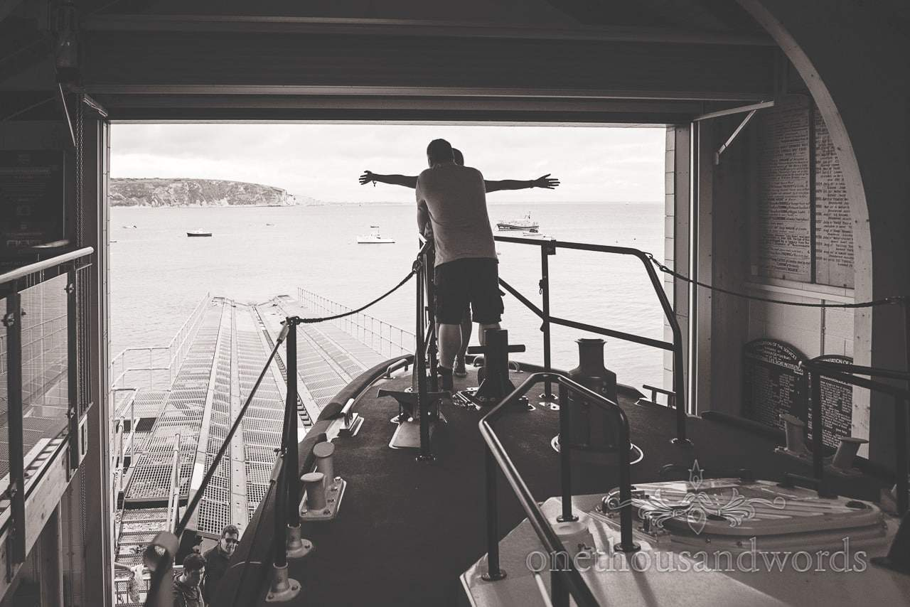 Black and white engagement photograph of couple replicating titanic film on lifeboat