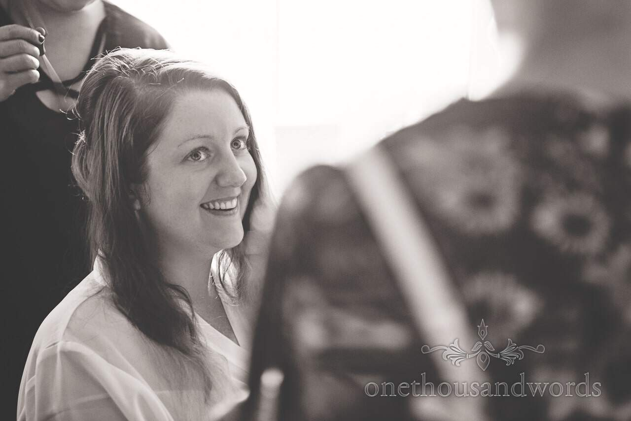 Black and white photograph of bride having hair styled before Lulworth Castle Wedding Photographs