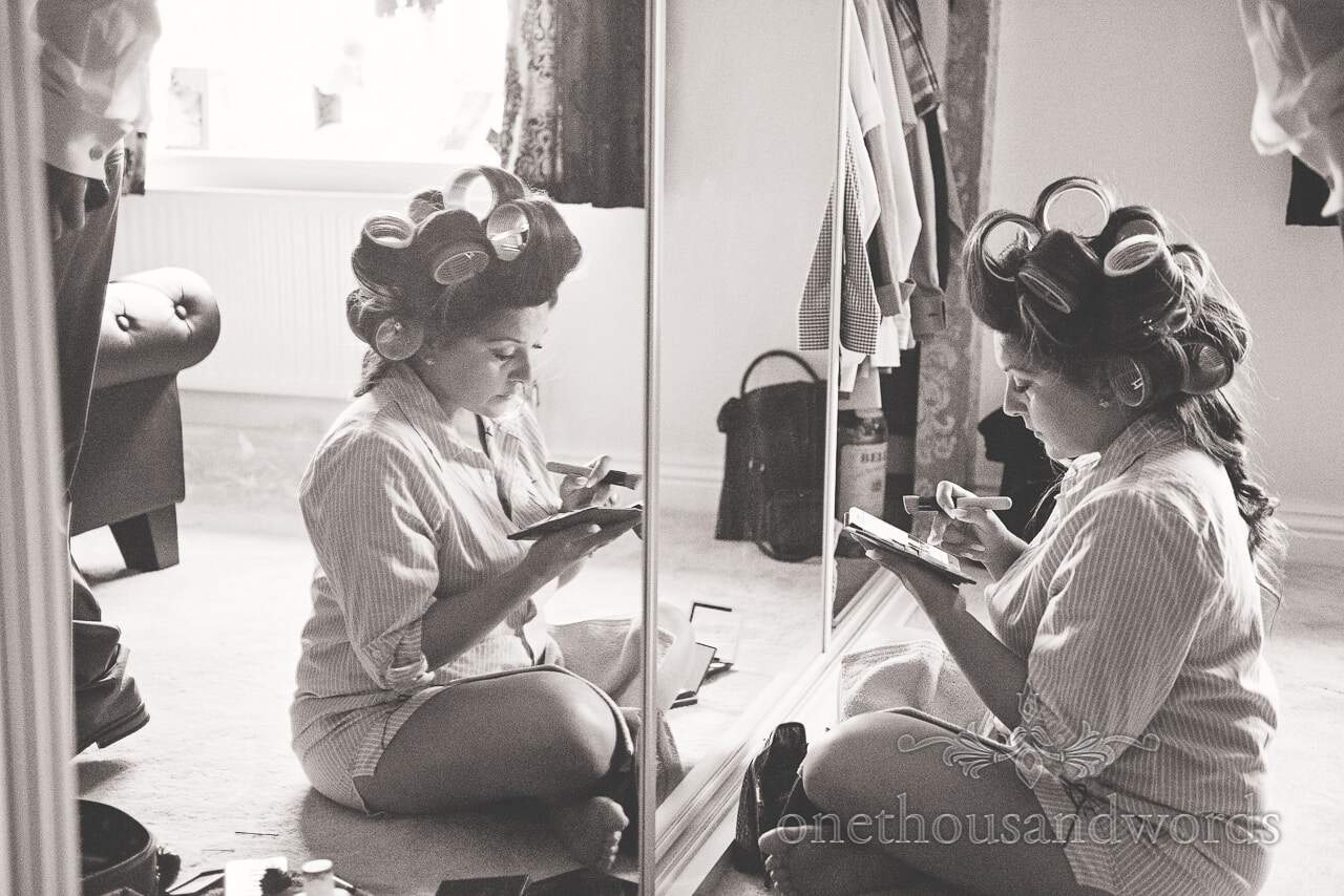 Black and white photograph of bride in curlers putting on wedding make up in mirror