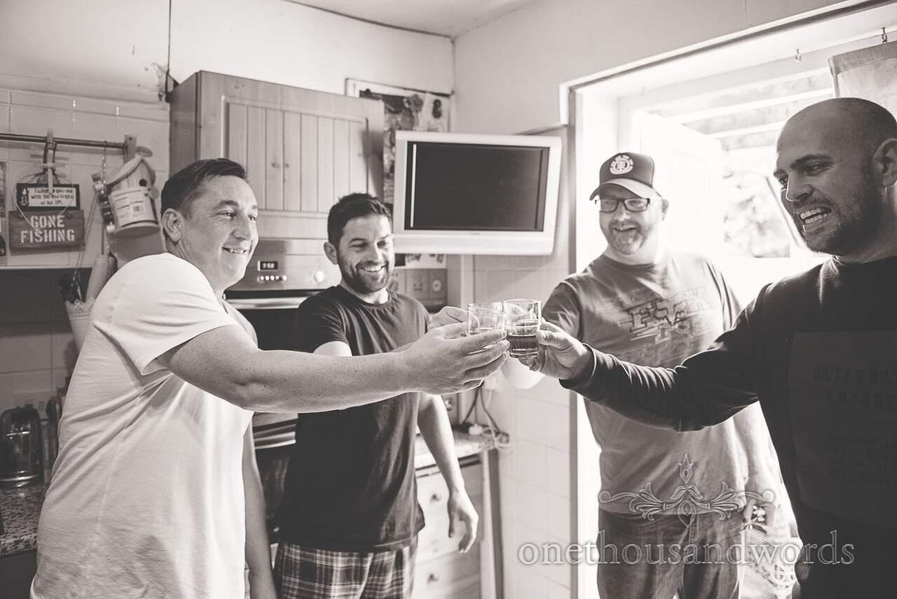Black and white wedding photograph of Groomsmen raise a toast on wedding morning in Dorset