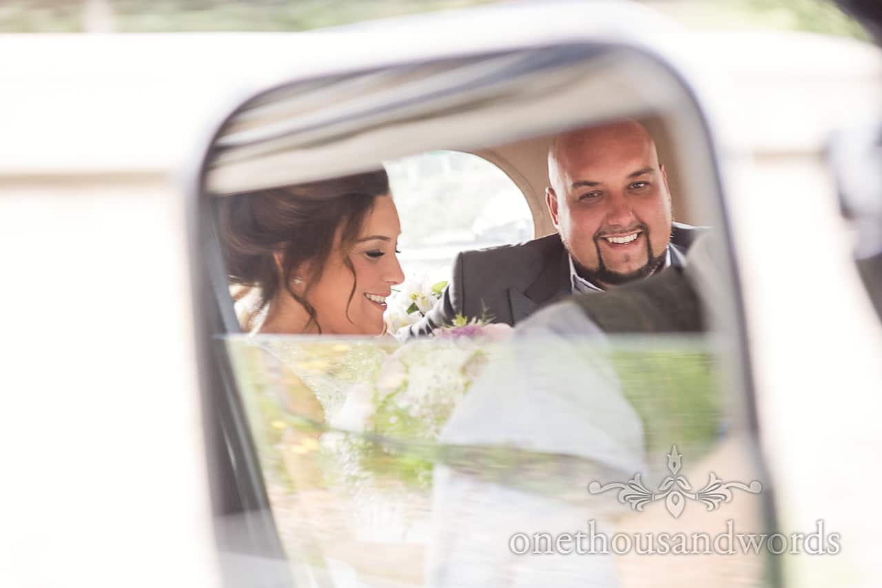 Bride and brother in wing mirror at wedding car at Highcliffe Castle Wedding