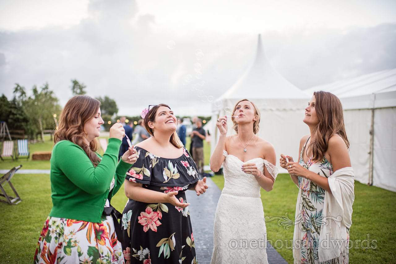 Bride and friends blow bubbles outside marquee at reception