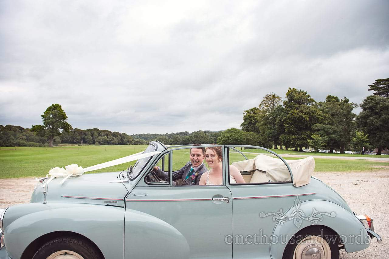Bride and groom arrive in classic Morris Minor at Lulworth Castle Wedding Photographs