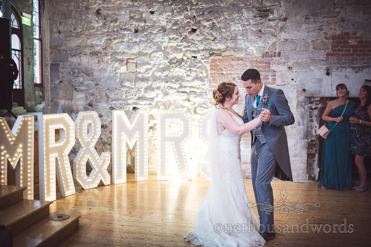 Bride and groom first dance with MR & MRS signs at Lulworth Castle Wedding
