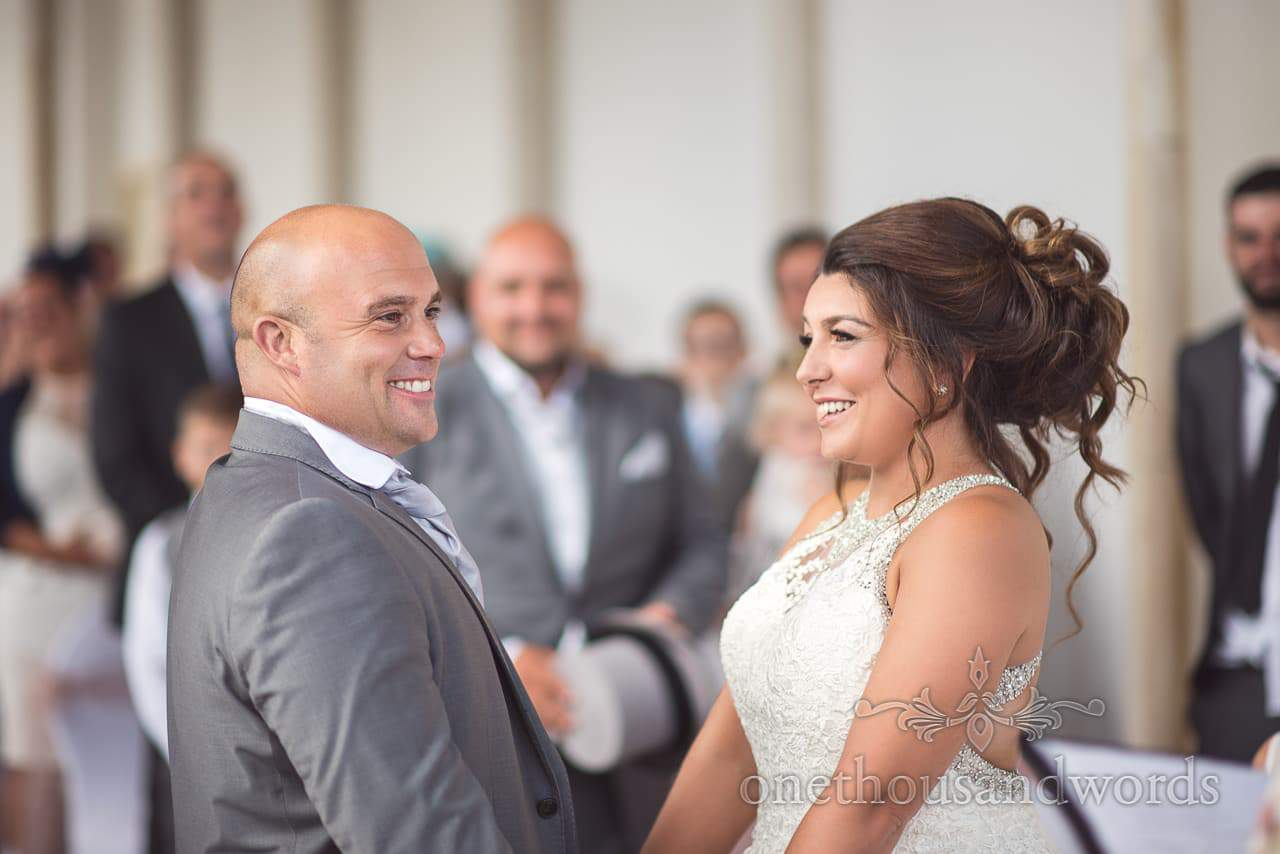 Bride and groom laugh during wedding ceremony at Highcliffe Castle Wedding