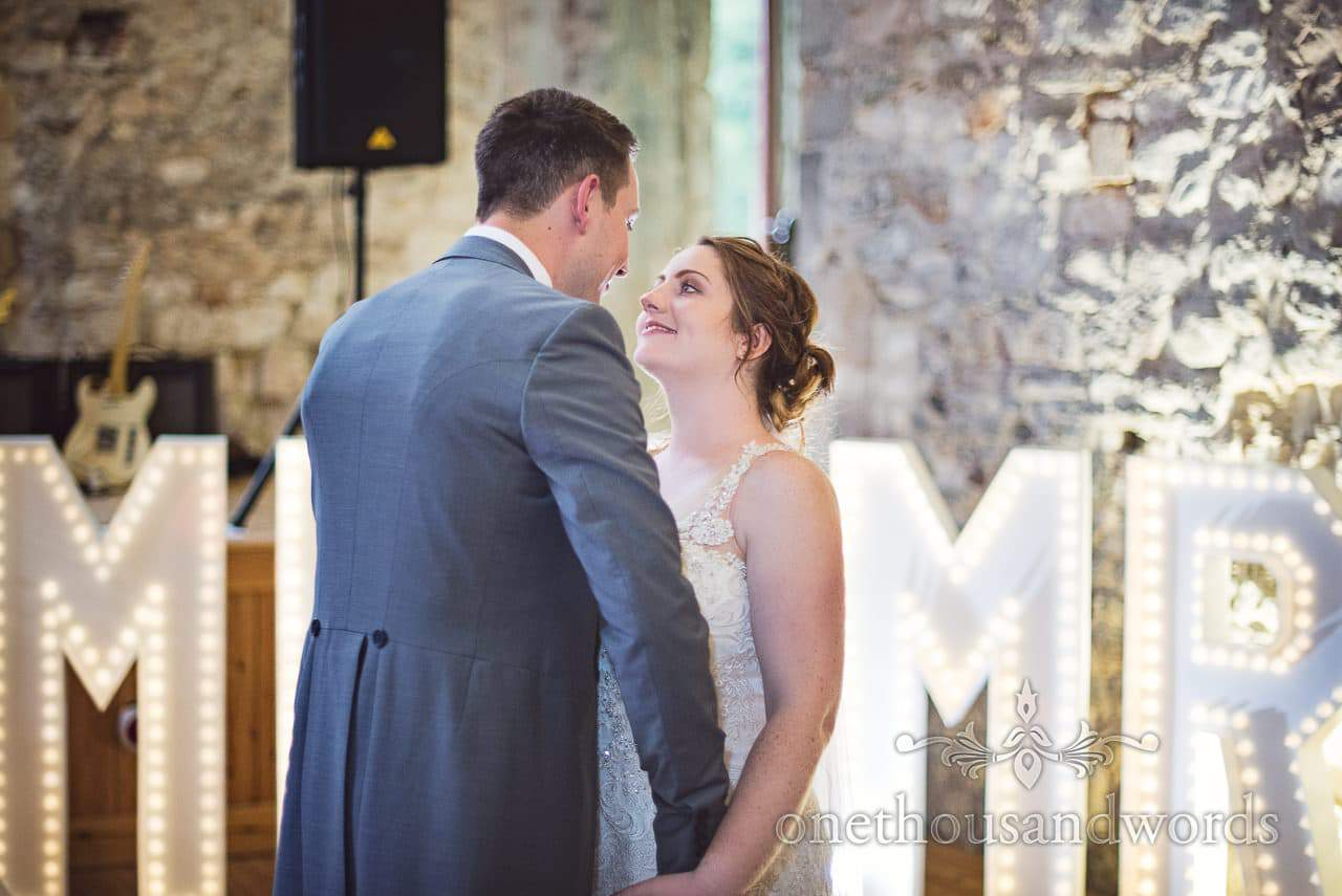 Bride and groom look into each others eyes at Lulworth Castle first dance