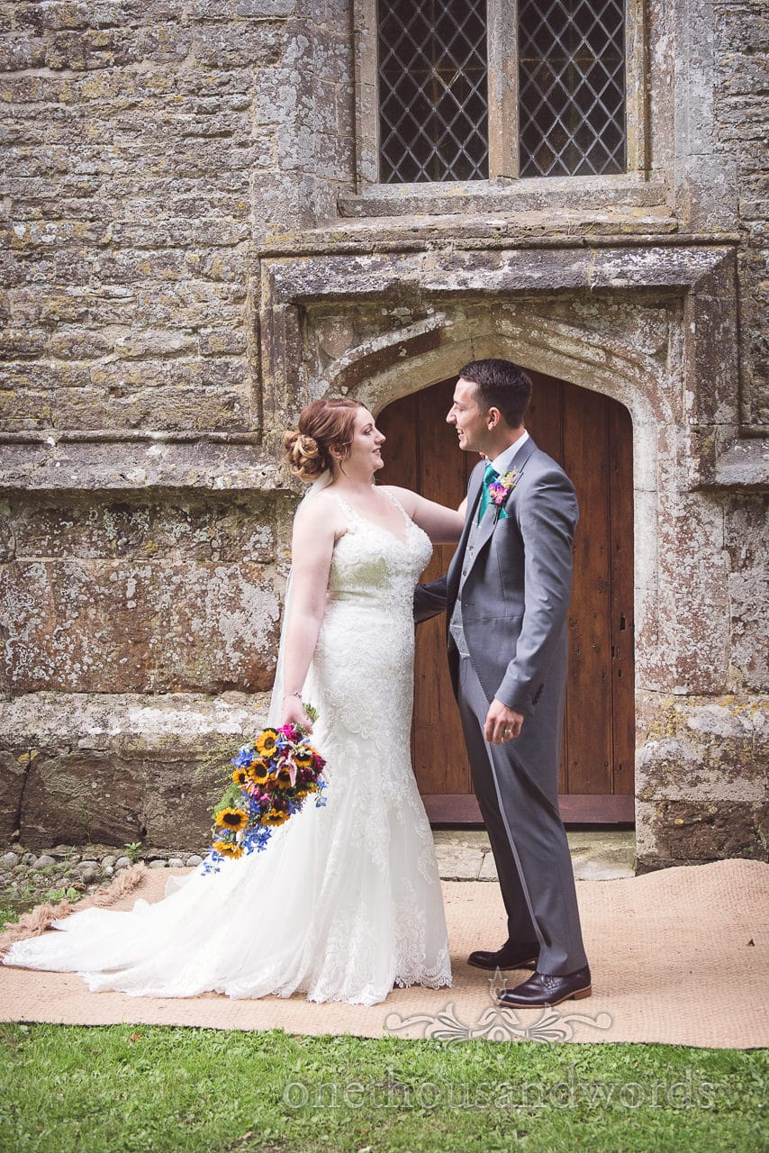 Bride and groom outside church doorway at Lulworth Castle Wedding Photographs