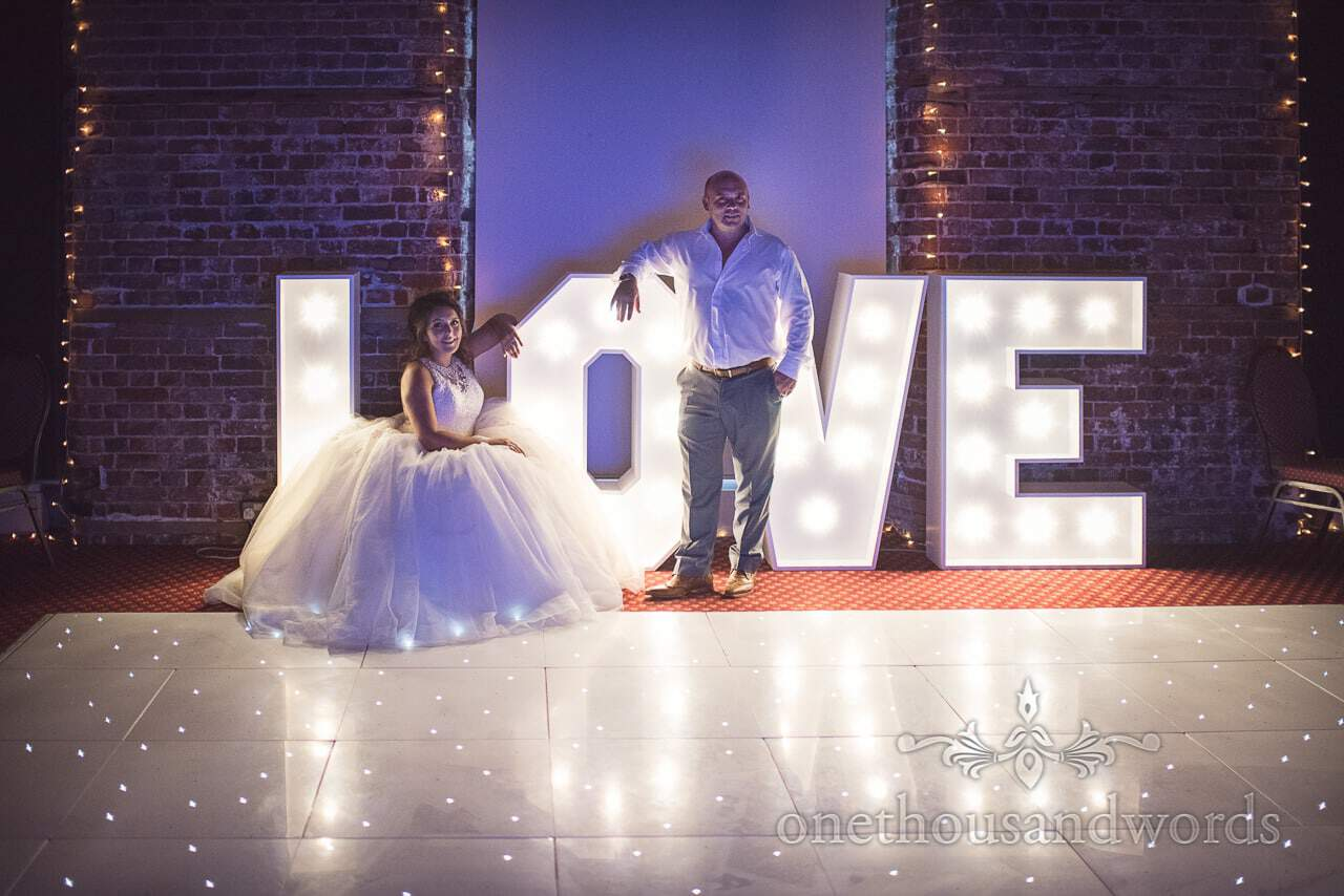 Bride and groom pose with LOVE sign and star dance floor at Highcliffe Castle Wedding