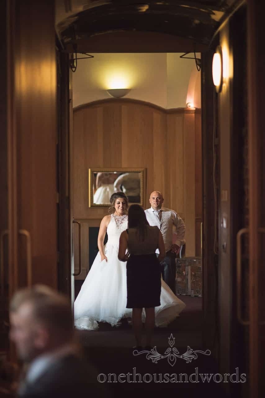 Bride and groom wait to be announced into wedding breakfast at Highcliffe Castle