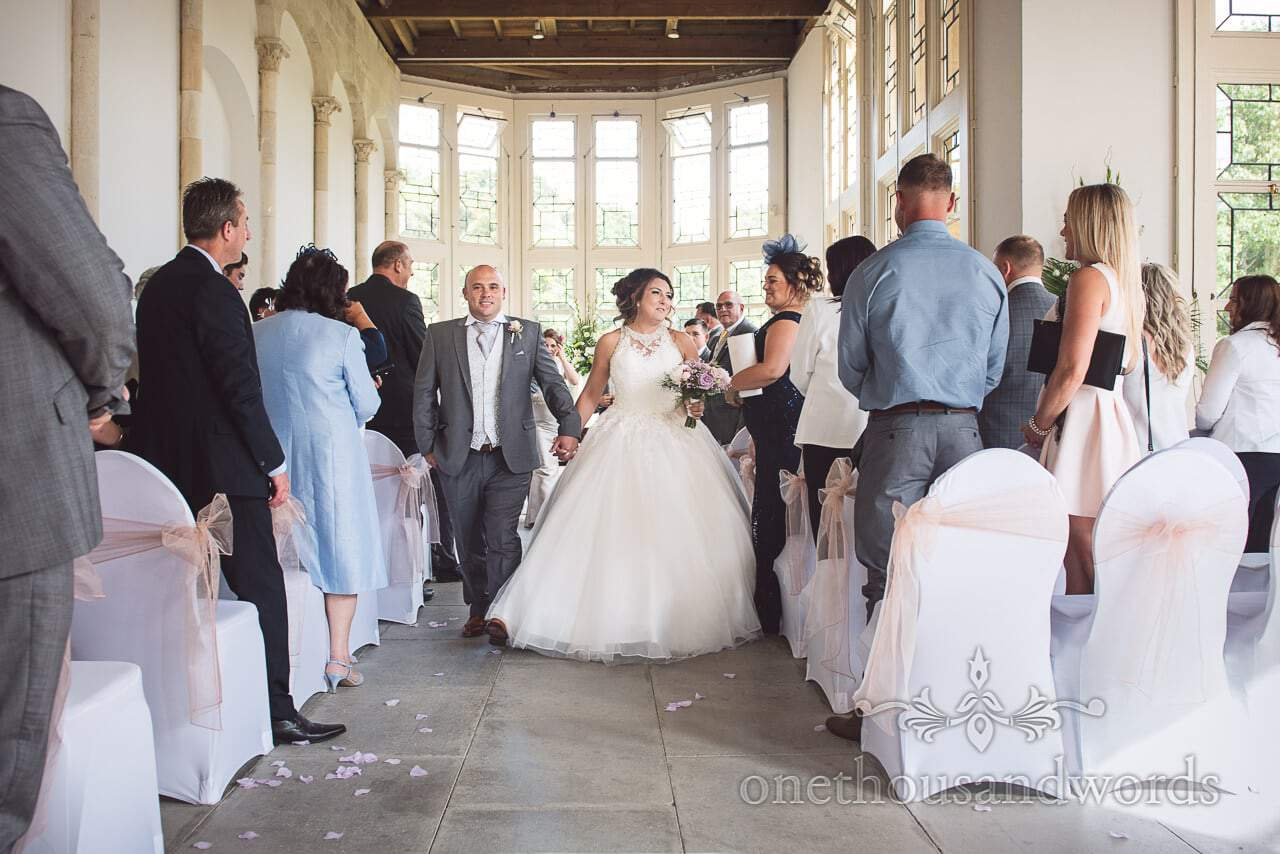 Bride and groom walk down the aisle at Highcliffe Castle Wedding Photographs