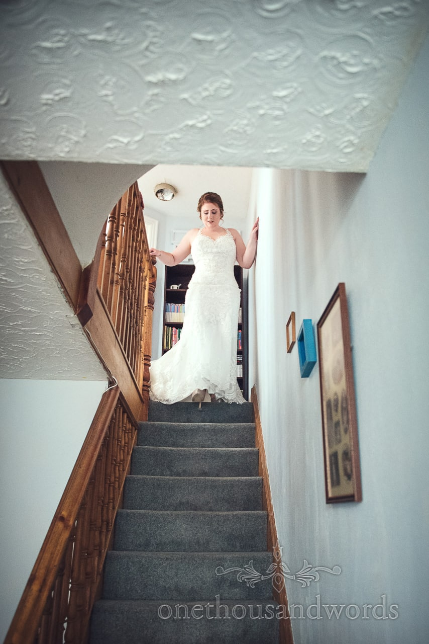 Bride ascends the stairs in lace detail wedding dress before Lulworth wedding