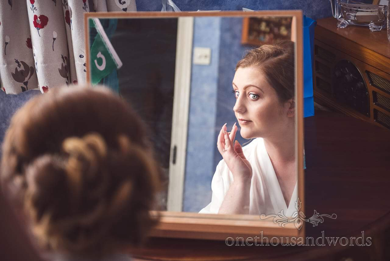 Bride checks herself in mirror on morning of Lulworth Castle Wedding Photographs