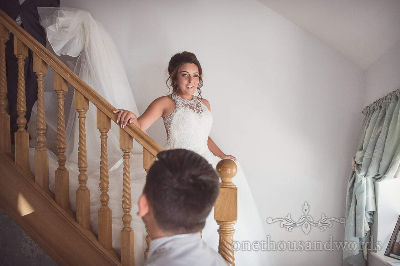 Bride descends stairs in wedding dress on wedding morning