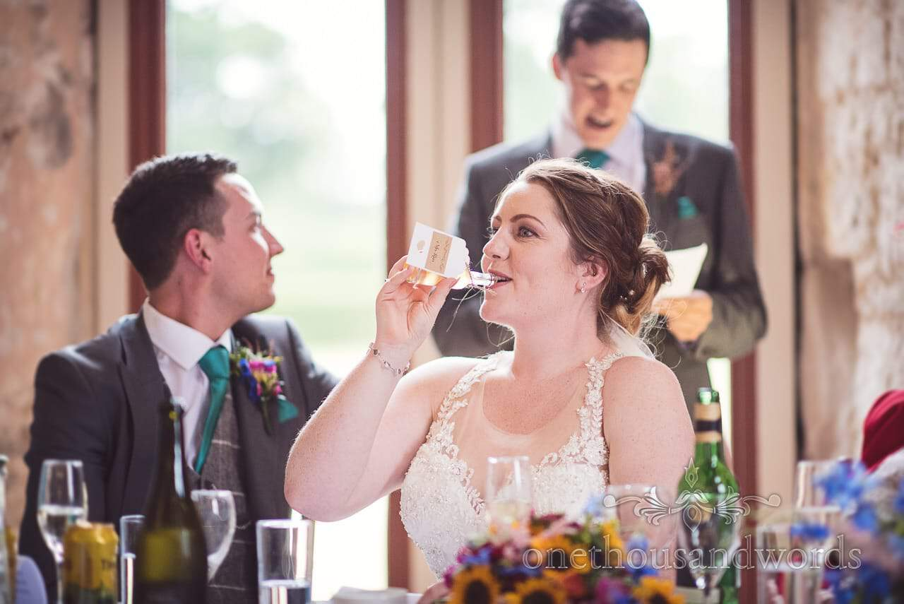 Bride drinks bottle of alcohol during wedding speeches at Lulworth Castle Wedding