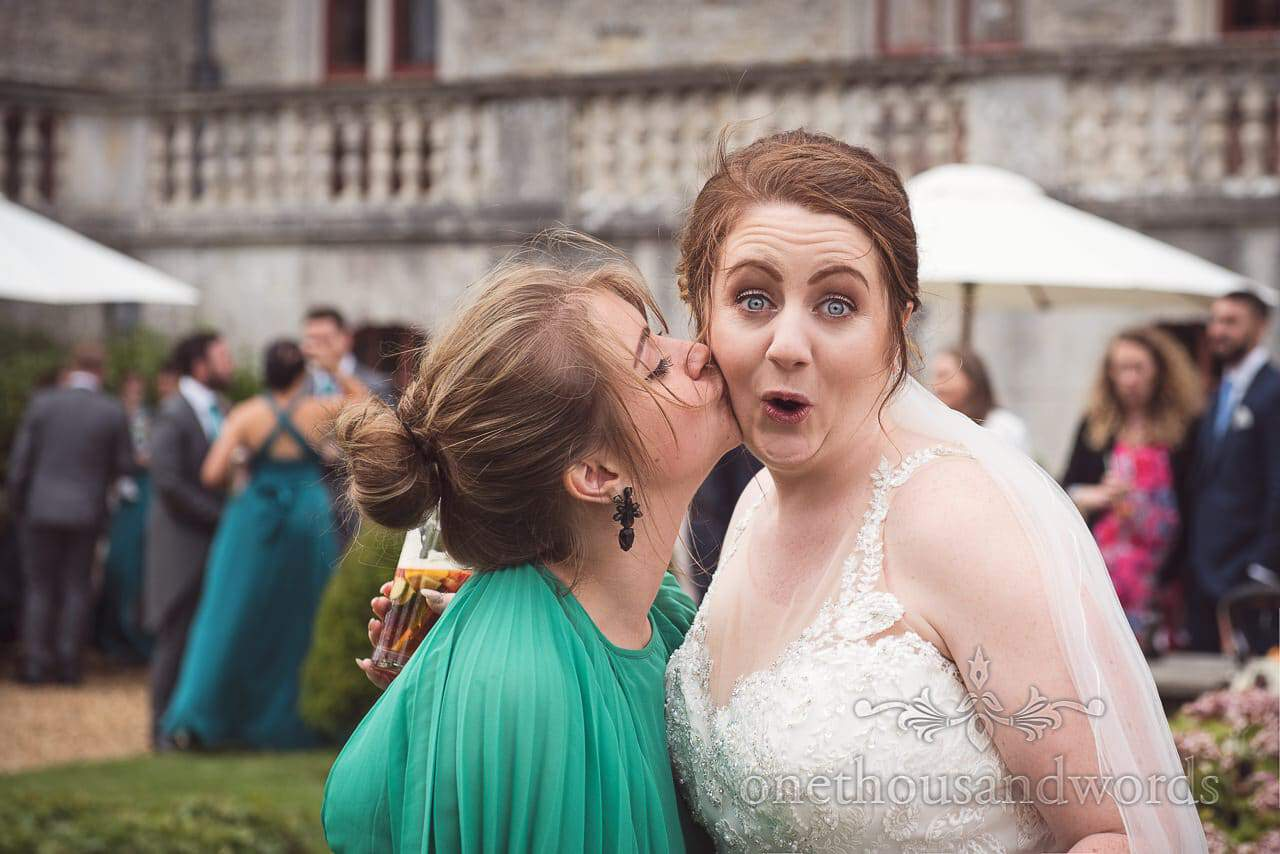 Bride gets a kiss from guest at Lulworth Castle Wedding Photographs