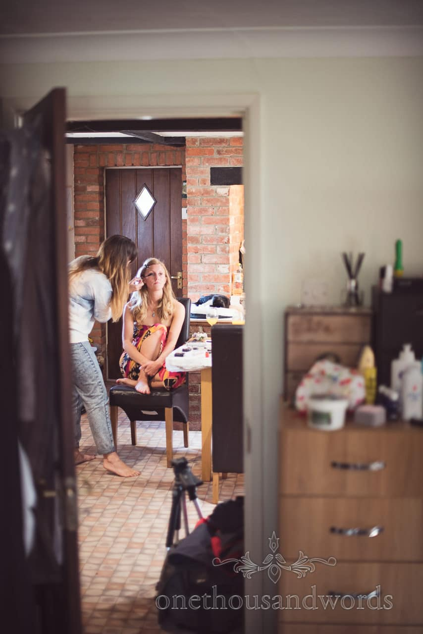 Bride has make-up styled looking through doorway on wedding morning at home in Dorset