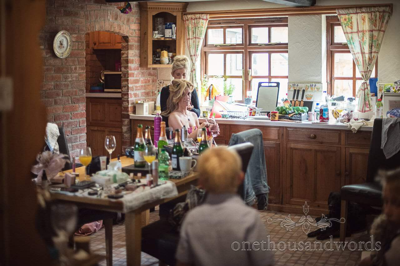 Bride has wedding day hair styled in country house kitchen on wedding morning