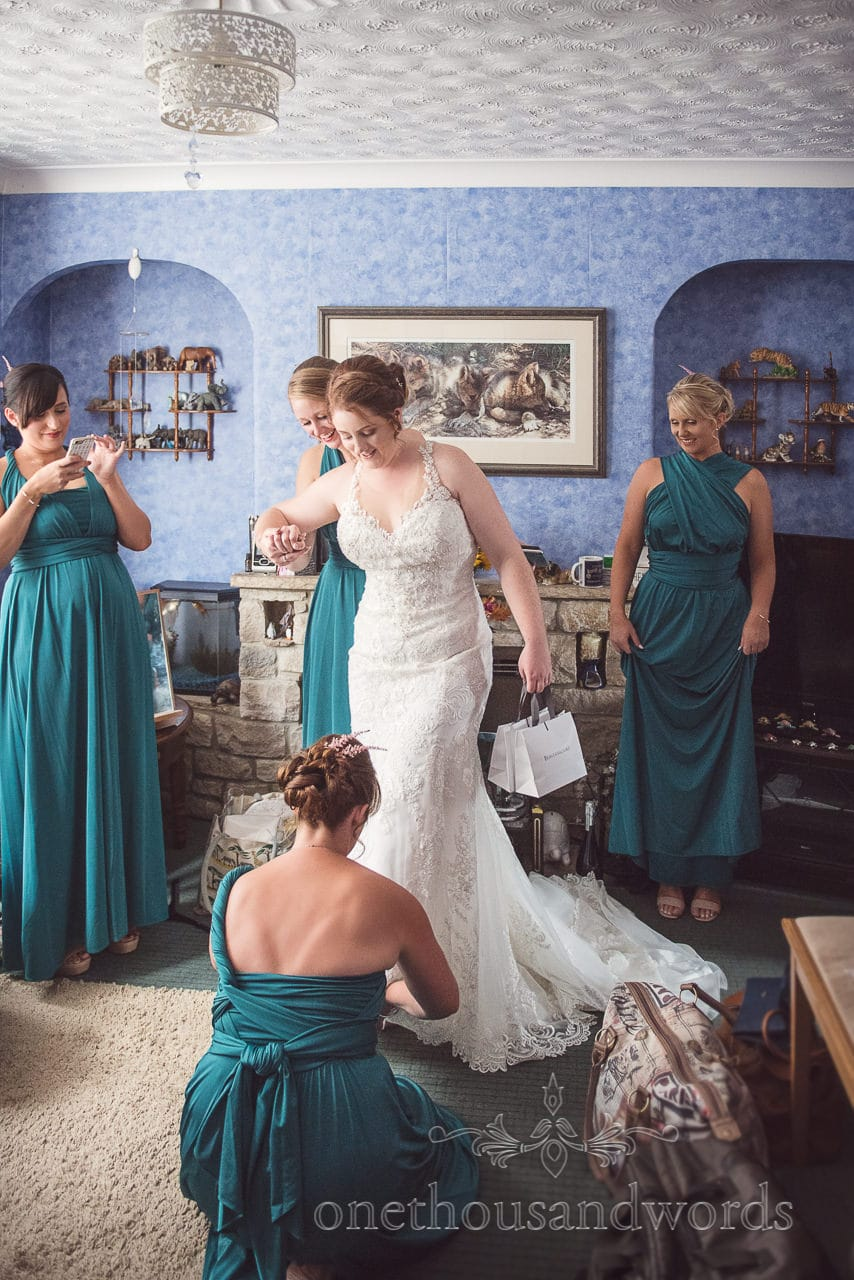 Bride helped with shoes by bridesmaid on morning of Lulworth wedding