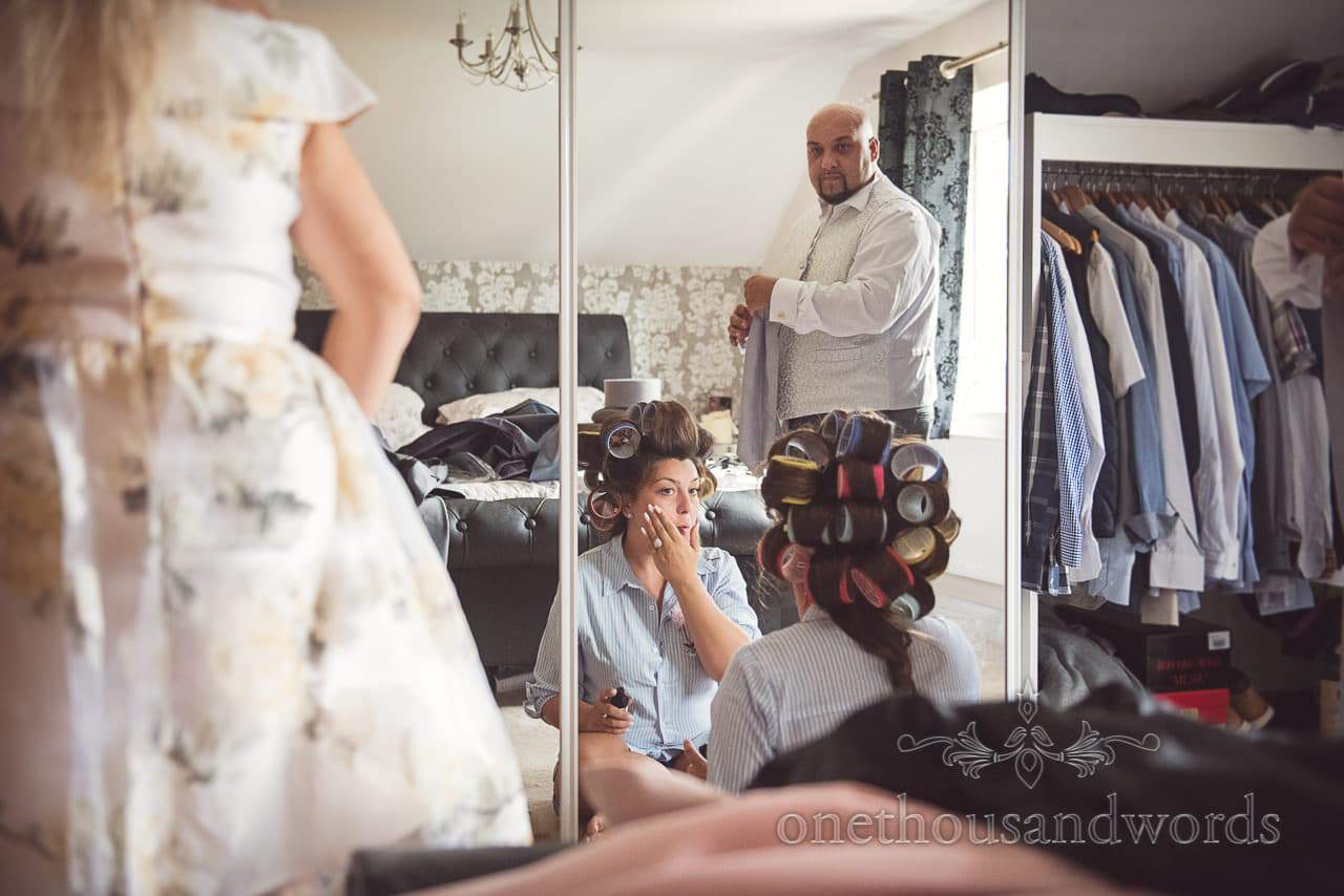 Bride in curlers applies wedding make-up watched by brother on wedding morning