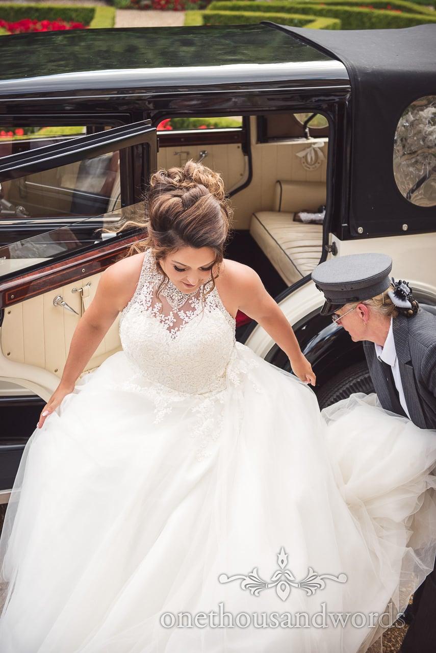Bride in white wedding dress exits classical wedding car at Highcliffe Castle Wedding venue