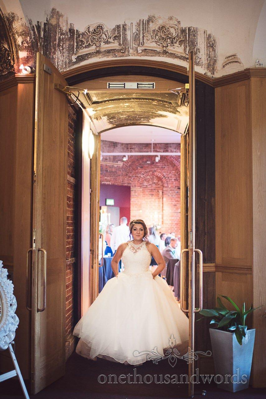 Bride in white wedding dress walks through doorway at Highcliffe Castle Wedding