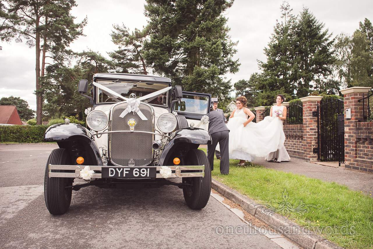 Bride is helped into classical wedding car by bridesmaid outside house