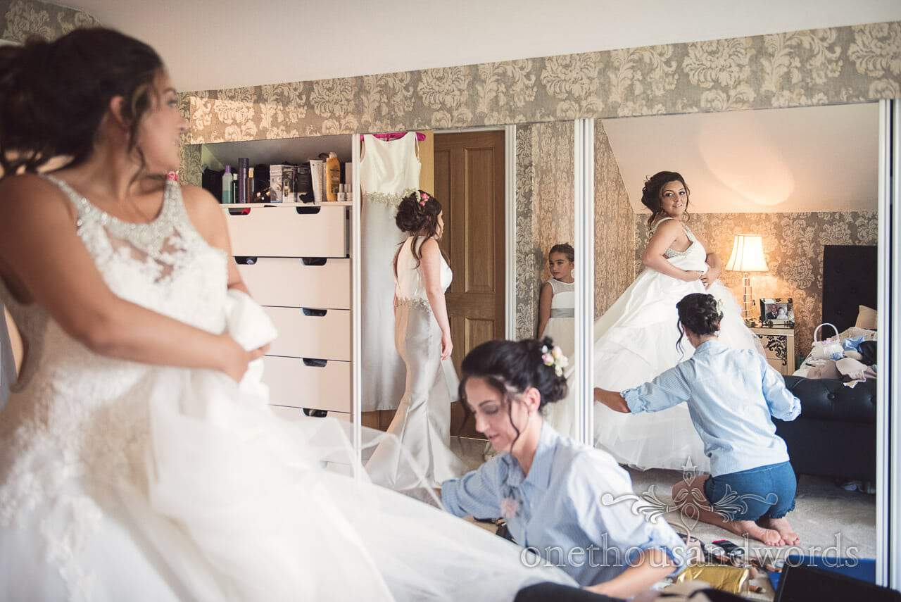 Bride is helped into her wedding dress on wedding morning in mirror