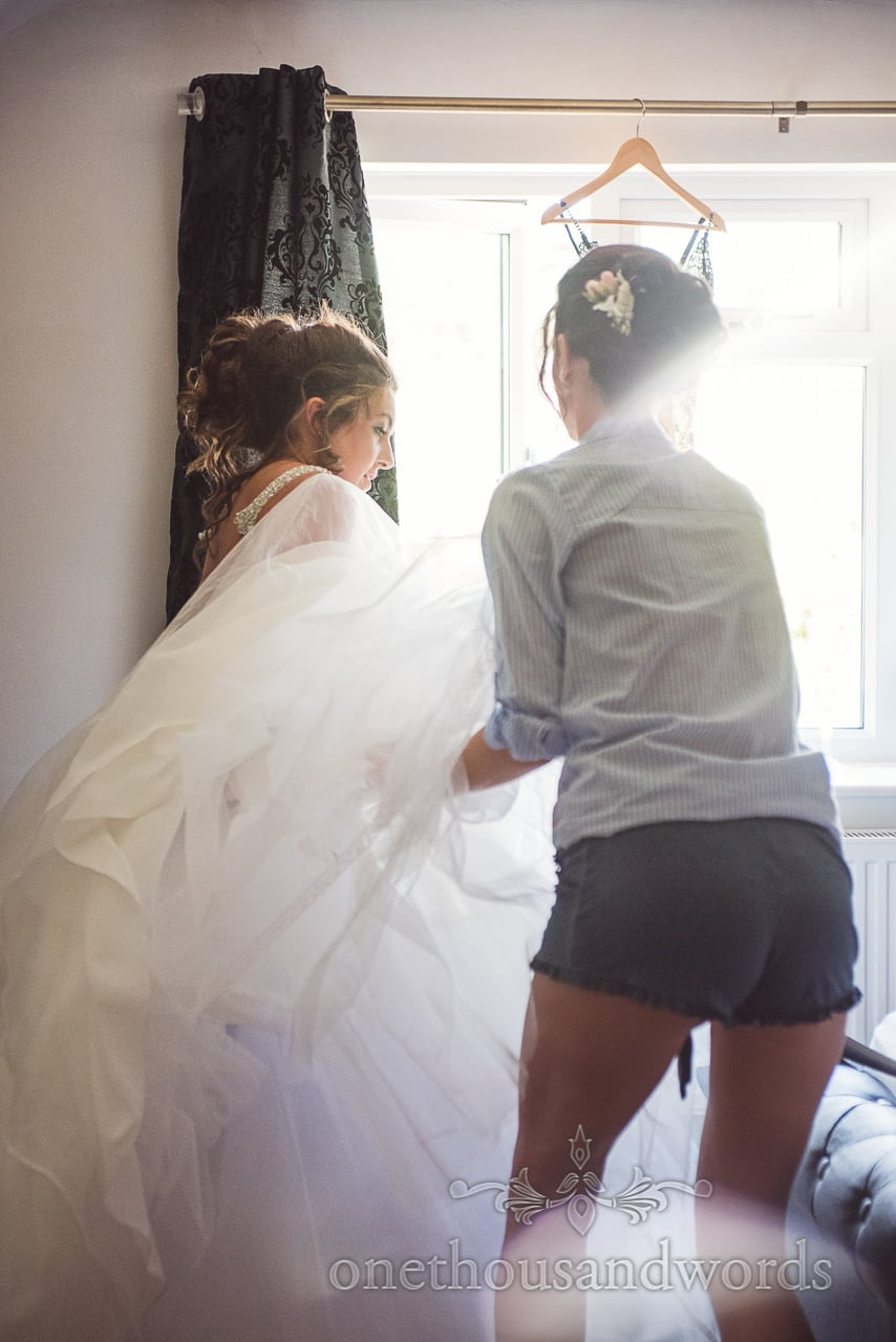Bride is helped into wedding dress by matron of honour on wedding morning