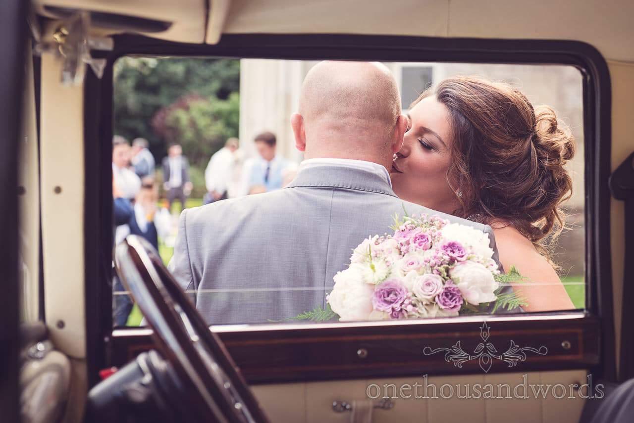 Bride kisses groom through wedding car window at Highcliffe Castle Wedding