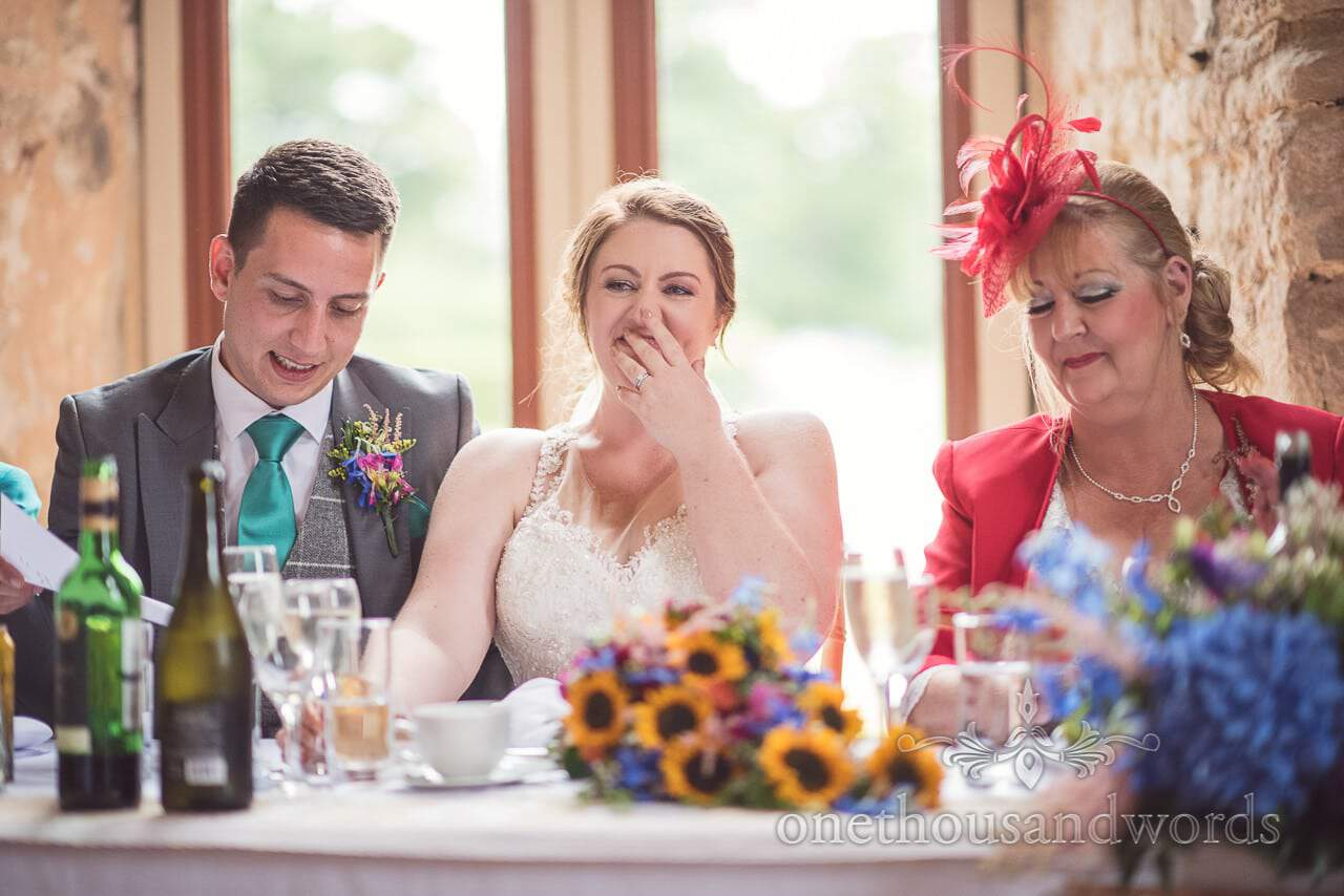 Bride laughing during speeches at Lulworth Castle Wedding Photographs