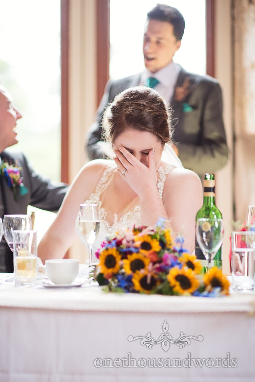 Bride laughs and hides her face during wedding speeches at Lulworth Castle Wedding