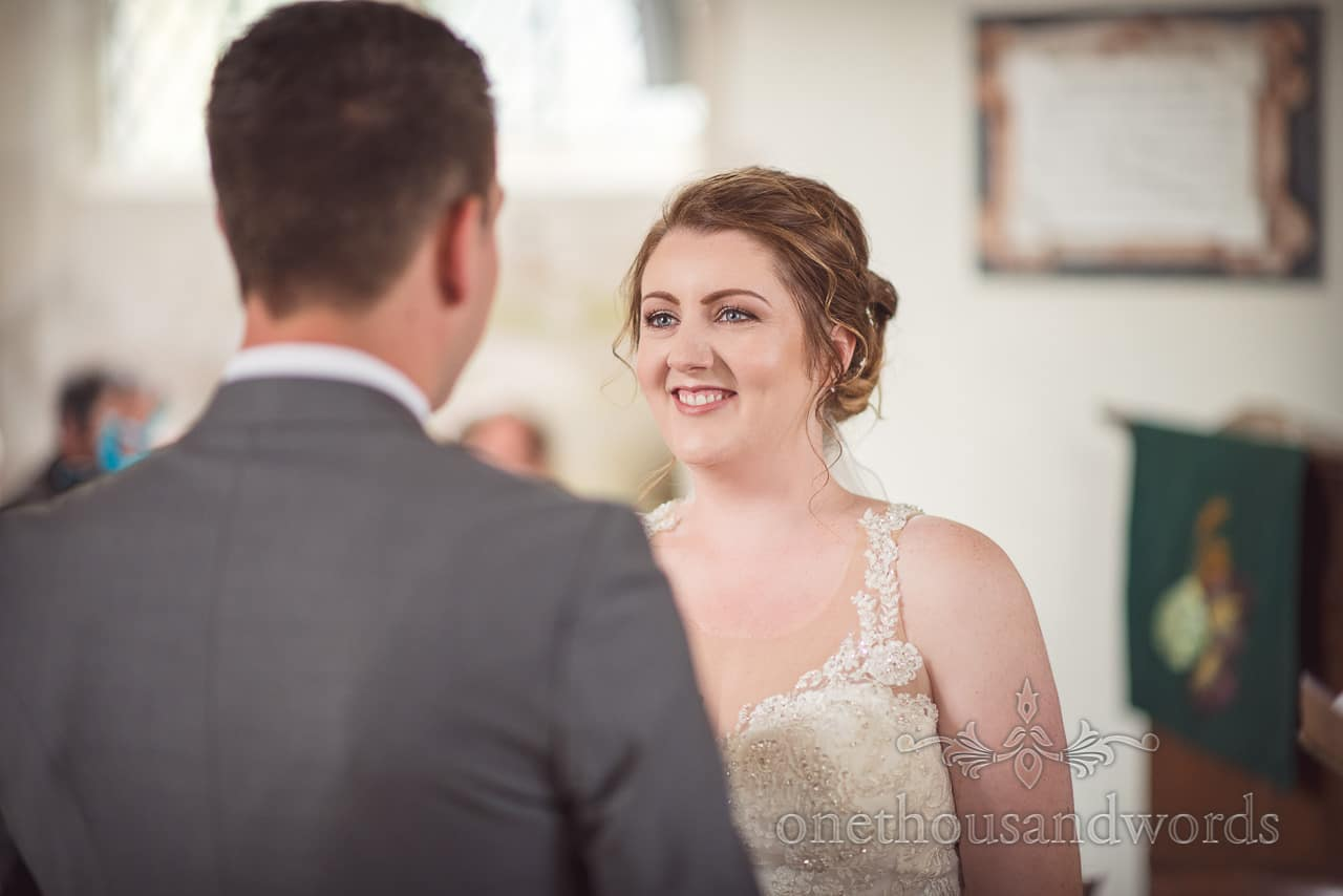 Bride looks at groom during church ceremony at Lulworth Castle Wedding Photographs