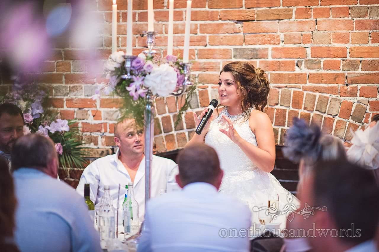 Bride makes wedding speech against bare brick wall at Highcliffe Castle Wedding