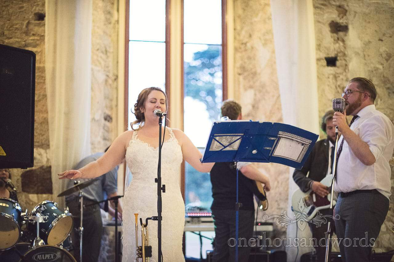 Bride sings with wedding band at Lulworth Castle Wedding Venue in Dorset