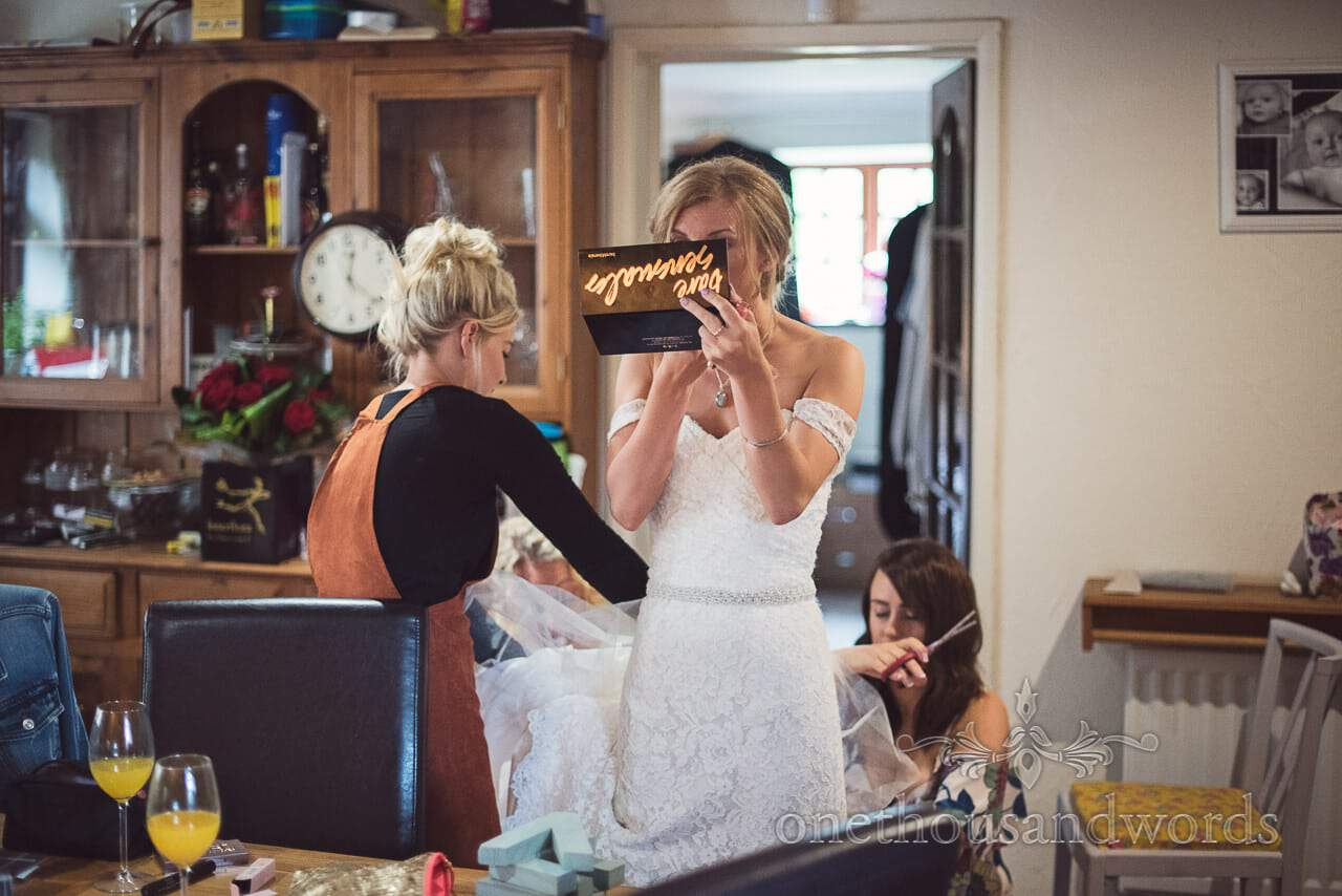 Bride styles her make up as her wedding dress is adjusted at home before wedding