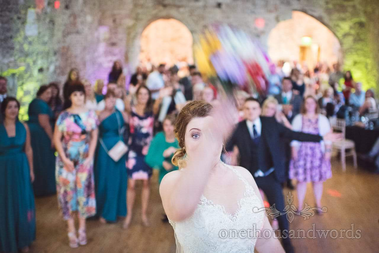 Bride throws multi coloured bouquet at Lulworth Castle Wedding