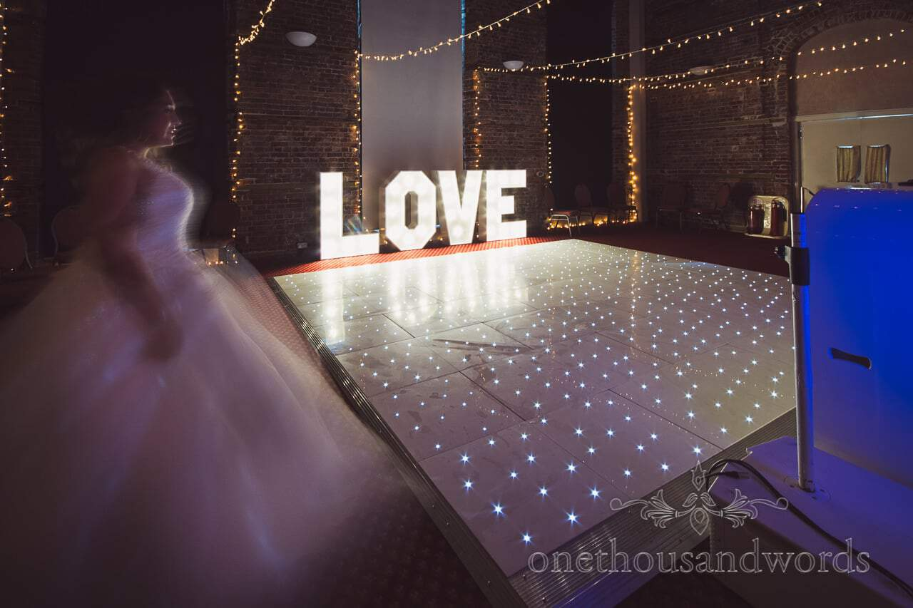 Bride with LED dance floor, LOVE sign and fairy lights at Highcliffe Castle Wedding