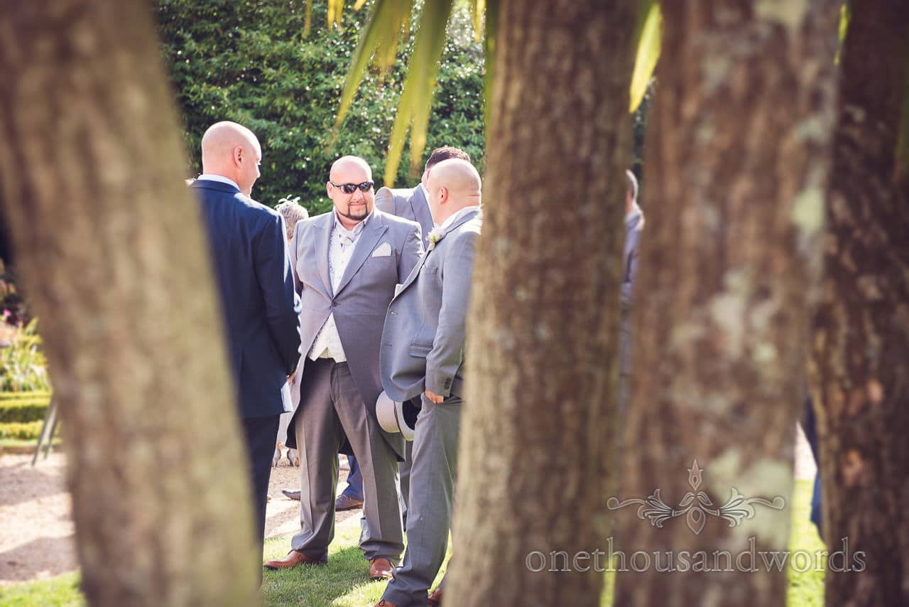 Brides brother enjoys drinks reception in the sun at Highcliffe Castle Wedding