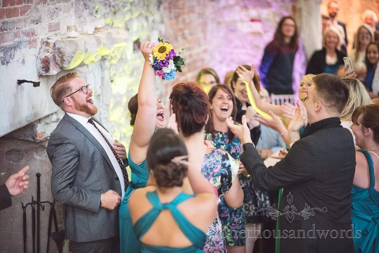 Bridesmaid catches wedding bouquet at Lulworth Castle Wedding Photographs