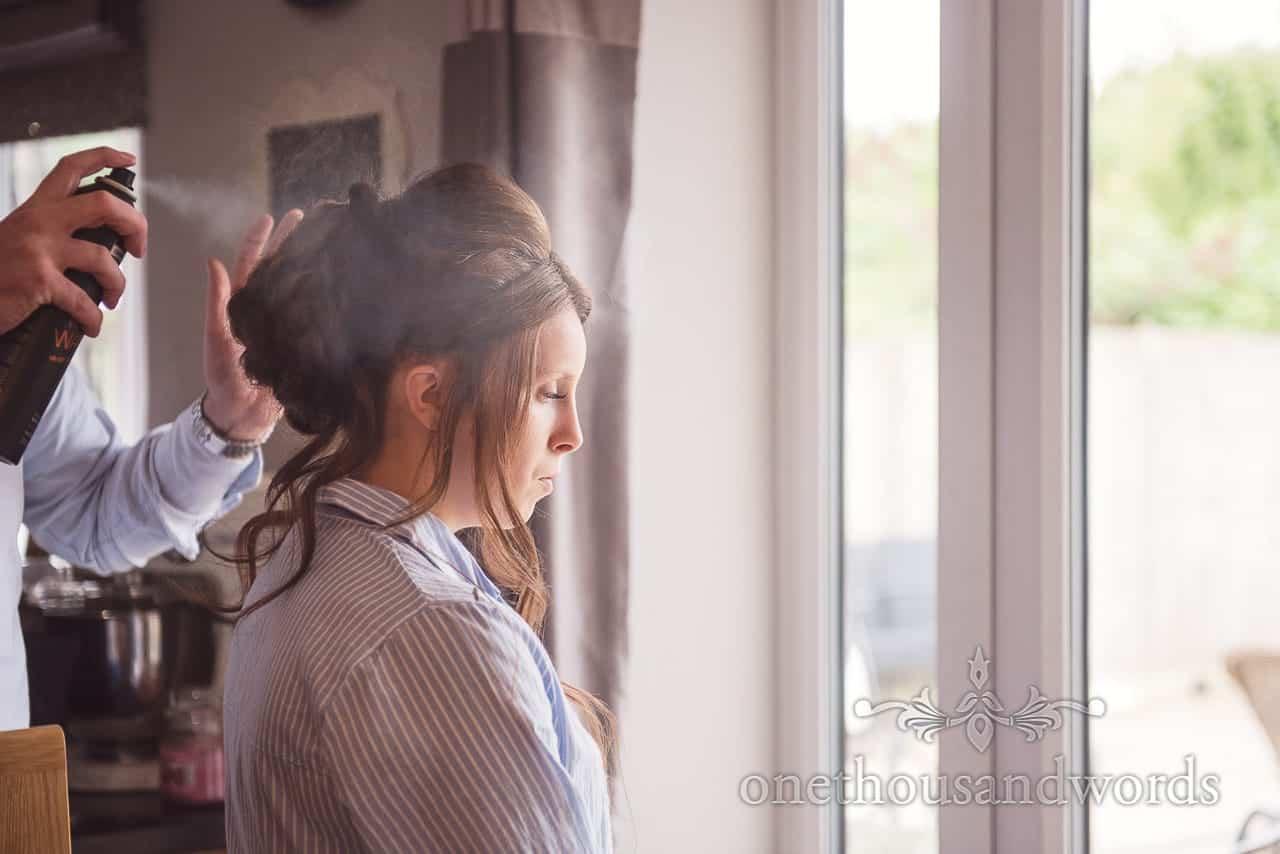 Bridesmaid has wedding hair sprayed during bridal preparations on wedding morning