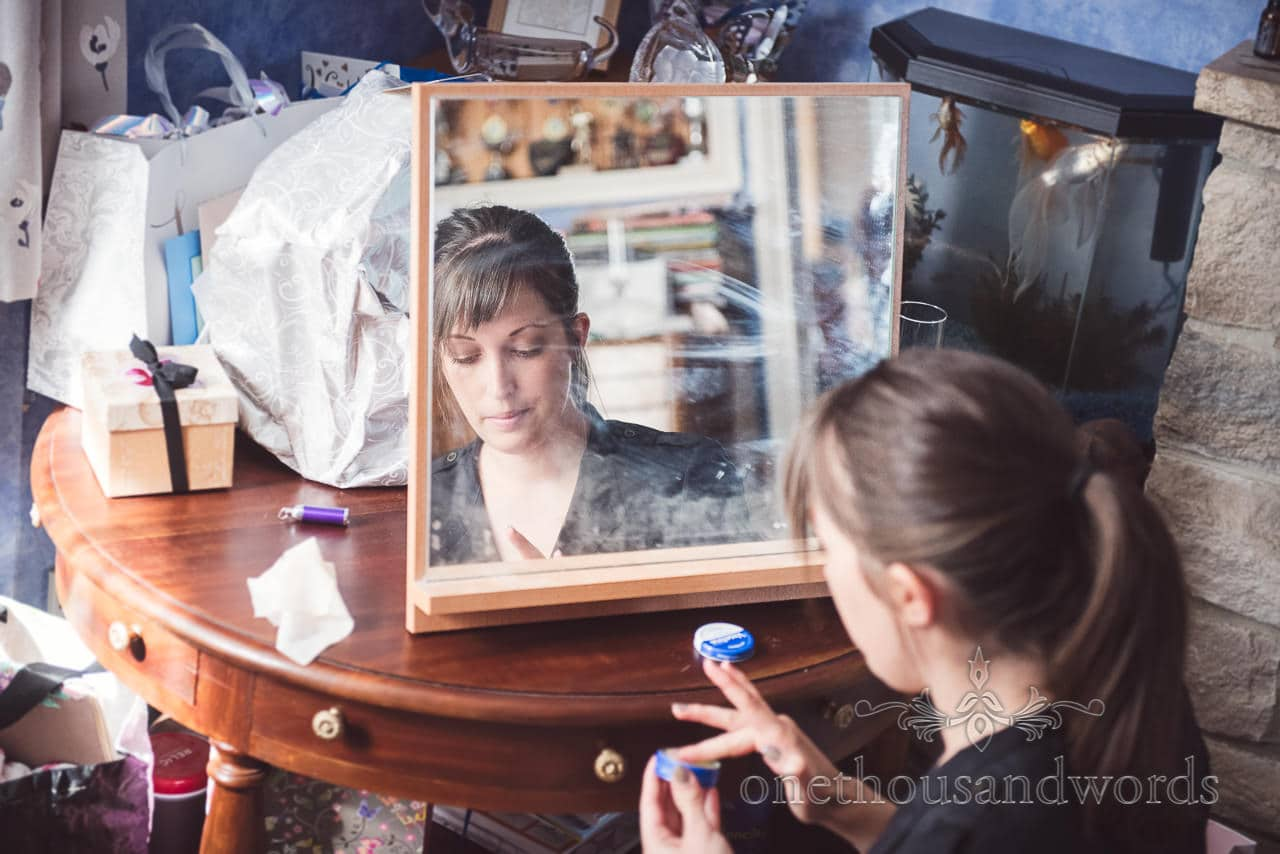 Bridesmaid in front of mirror during wedding preperation