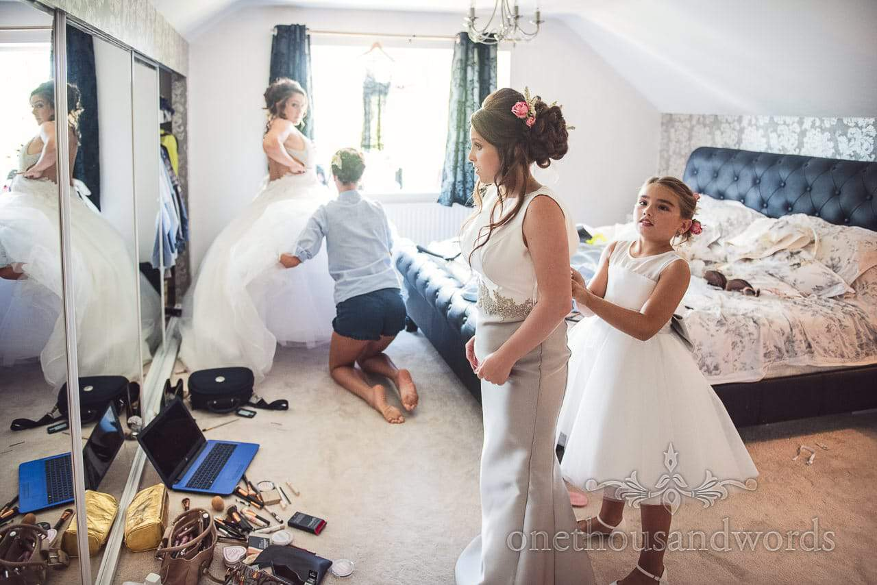 Bridesmaid is helped into her dress as bride is helped into her wedding dress